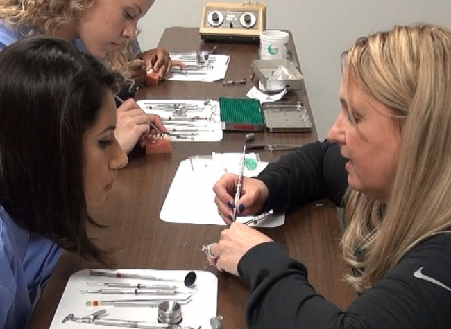 dental instructor showing proper cleaning technique to student