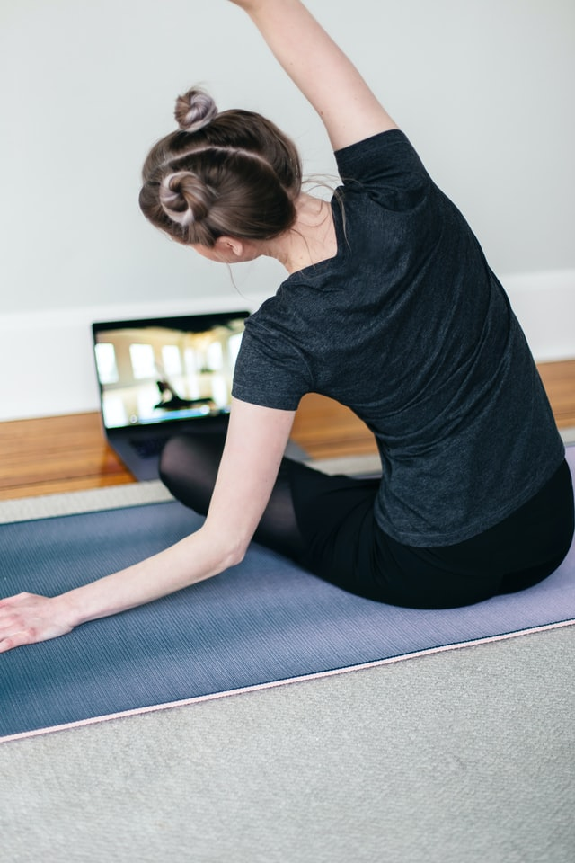 Woman stretching at home with a virtual class.